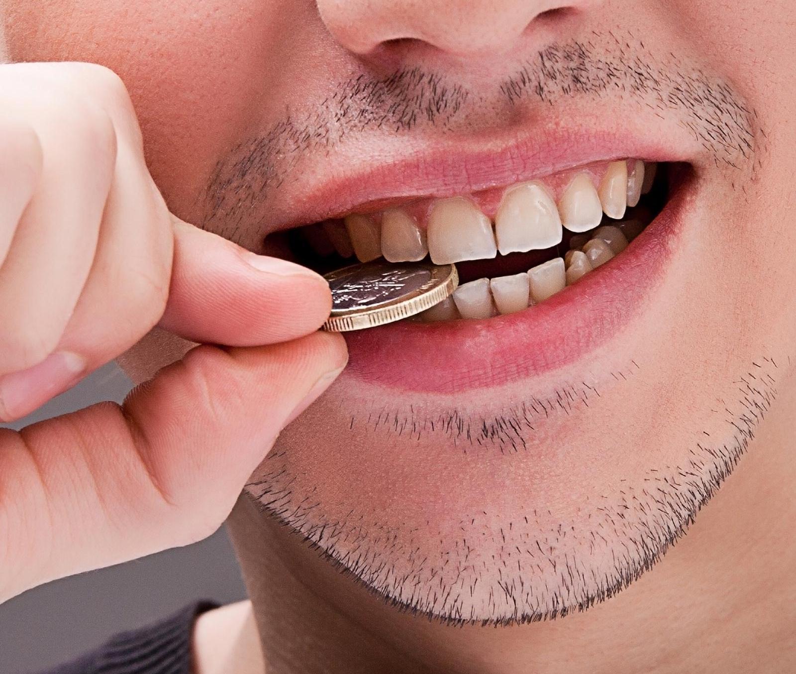 Mann testet Authentizität von Geldstück